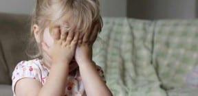 Girl hides her eyes behind her hands - photo: AnneMS on Shutterstock.com