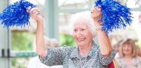 Older woman celebrating with blue pompoms