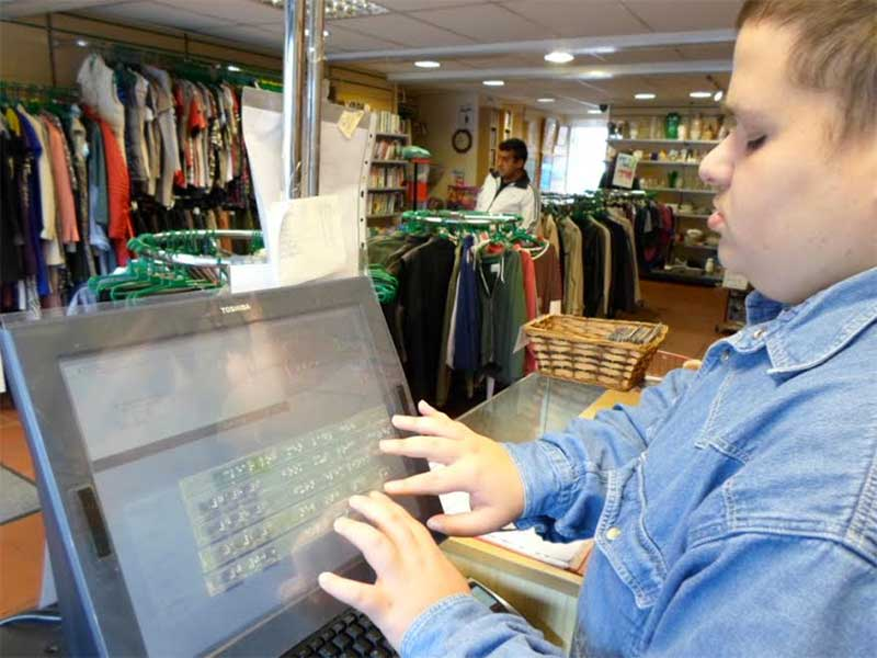 Volunteer Harry uses the braille till overlay at a WESC Foundation shop